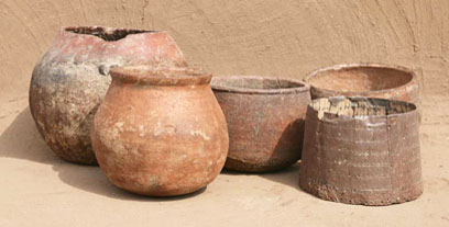 Traditional pottery and date measure (right)