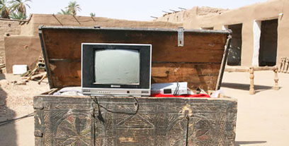 Carved wood chest, with TV and satellite reciever found inside.
