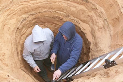 Mark Macklin and Jamie Woodward examining layers of sand and river silt