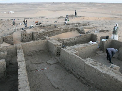 The later houses, excavated in 2009, with the earlier walls beginning to appear (behind scale)