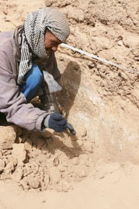 Mekawi Abdel Rahman removing rubble from the plaster walls
