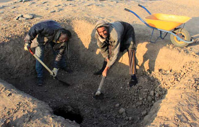 Rami Mohamed Abdu and Abou Ad Abu Taher excavating through the roof of the western chamber