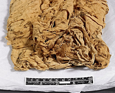 The textile looks quite soft and flexible, but also appears very fragmentary, with some sections potentially joined to each other by a mere few threads. The newer looking thread is among the folds at the bottom. © Norwich Castle Museum and Art Gallery / Trustees of the British Museum
