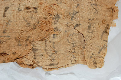 View of the reverse of the fabric, with the black ink of the hieroglyphs soaked through the linen. © Norwich Castle Museum and Art Gallery / Trustees of the British Museum