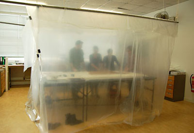 The conservators work in a tent in order to raise the relative humidity and prevent brittle fibres from splitting. © Norwich Castle Museum and Art Gallery / Trustees of the British Museum.