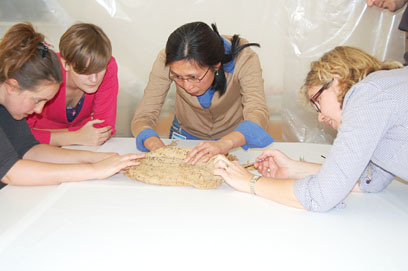 British Museum and NMAS conservators start to unfold the shroud. © Norwich Castle Museum and Art Gallery / Trustees of the British Museum