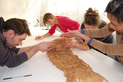 The conservators unfold one section of the shroud. © Norwich Castle Museum and Art Gallery / Trustees of the British Museum.