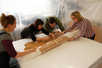 The conservators unroll sections of the shroud. © Norwich Castle Museum and Art Gallery / Trustees of the British Museum.