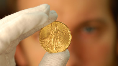 Ian Richardson holds up one of the gold coins. © Portable Antiquities Scheme
