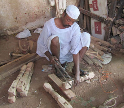 Craftsman cutting legs for a new angareeb, in Omdurman market near Khartoum