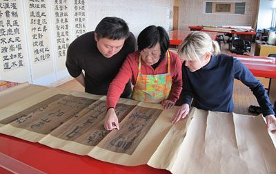 Zhu Pin Fang, Head of the conservation studio (centre), Valentina (right) and her colleague Shaozen assess the scroll before treatment