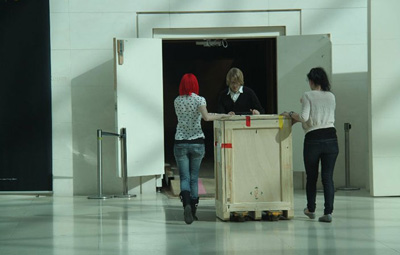 A crate containing one of the objects is wheeled into the exhibition space.