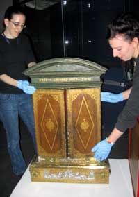 Morn Capper and Museum Assistant, Alex Garrett install one of the objects.