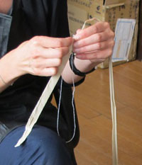 Treated silk is tied at the centre of the cord to fasten the hanging scroll.