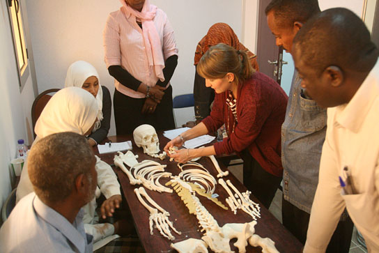 Workshop participants learning anatomy using a plastic skeleton.