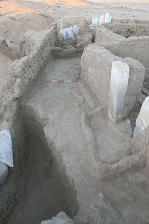 View west down street, with door into house E13.4, and pit through street deposits