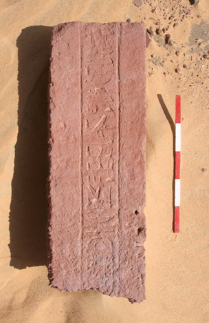 Sandstone doorjamb (F990) with badly eroded hieroglyphs