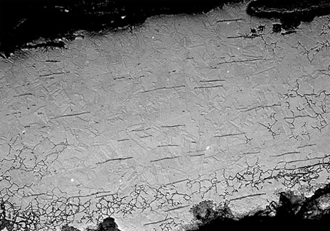 A high magnification scanning electron microscope (SEM) image of a copper alloy sample from one of the cauldrons. Darker horizontal lines were caused by many cycles of working and heating