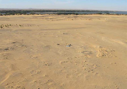 The low mounds of cemetery C mark graves, with the town in the background, before the Nile