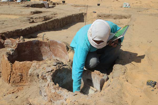 Shadia excavating ovens associated with house E13.5