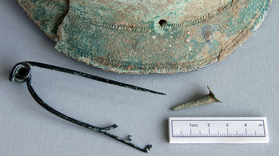 The helmet and brooch. © Canterbury Archaeological Trust Ltd