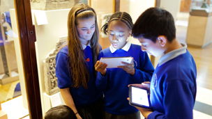 A group of children using tablets in the museum gallery
