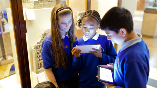 A group of children using a tablet in a Museum gallery