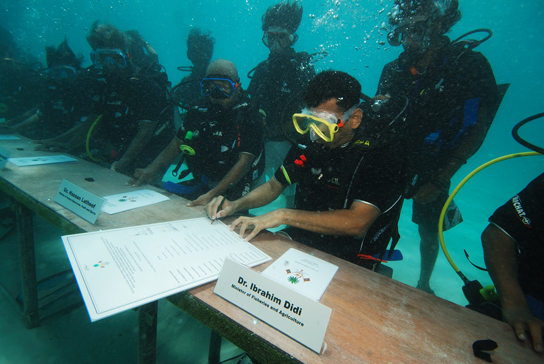 Government of the Maldives hold a cabinet meeting underwater to raise awareness of global sea level rise. © Mohamed Seeneen