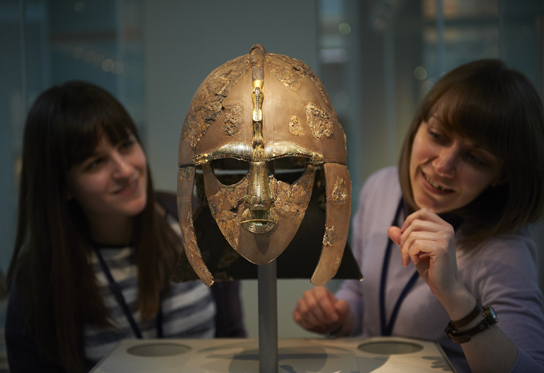 Curators Sue Brunning (r) and Rosie Weetch (l) installing the Sutton Hoo helmet in the gallery