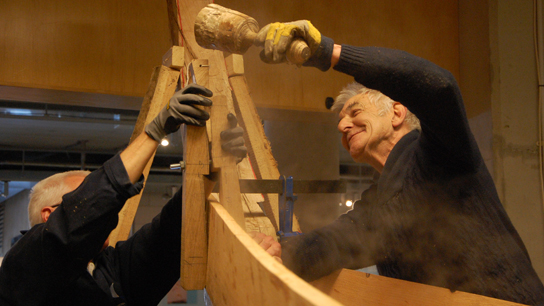 Brian and Mike fitting a plank with a traditional wooden clamp, tightened by driving in a wedge.