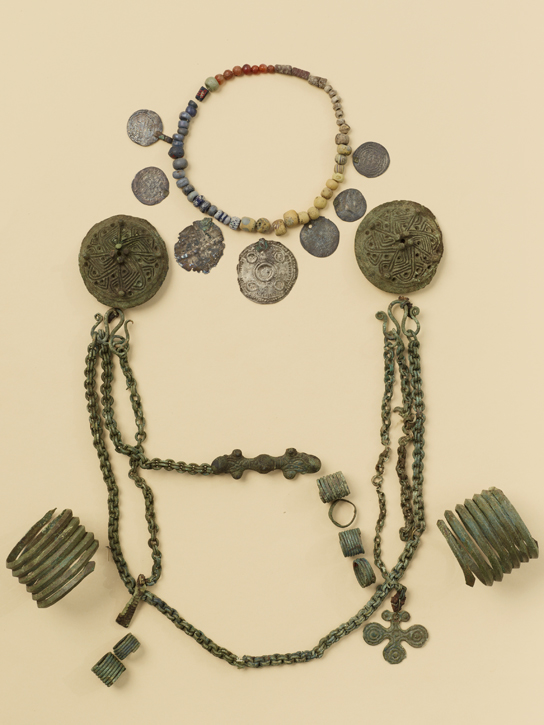 Female burial assemblage with a pair of round brooches, chain ornaments, equal-armed brooch, pendants, arm-rings and finger rings, AD 1050 – 110. Grave C23, Kjuloholm, Kjulo, Finland. © Suomen Kansallismuseo, Helsinki