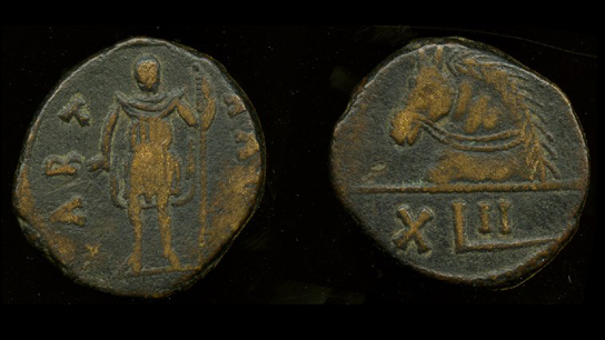 Copper 42 nummi coin showing a Vandal warrior. Although it does not carry a king's name, it is possible that this coin was made during the time of Gelimer (AD 530-3), and thus he may be the intended identity of the cloaked figure with a spear. The reverse shows the mark of value in Roman numerals (including the long-tailed L (=50) typical of Latin inscriptions in Vandal Africa, and also seen on Gelimer's silver coinage). Above is the fine image of a horse's head, the traditional emblem of Carthage since Punic times. TC,p241.2.Car