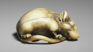 carved netsuke in the form of a sleeping rat