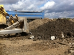 A bulldozer searches for the boards at the bottom of the tipped pile of clay.