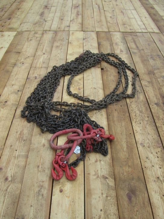 Crane lifting chain on the site floor.