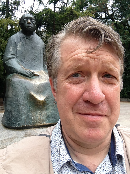 Paul Kobrak, being photobombed by Kathe Kollwitz in Kollwitz Platz, Prenzlauer Berg district, Berlin.