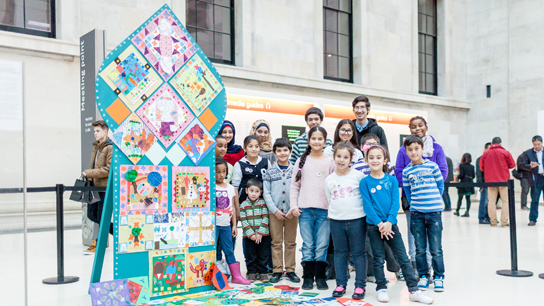 Young people from IYDA next to their art installation 'Reimagining the Palace of Persepolis' in the Great Court. Photo © Benedict Johnson