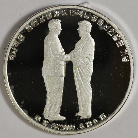 Silver coin commemorating the meeting of the leaders of South and North Korea in 2000, Pyongyang, DPRK, 2000. In June 2000 South Korean president Kim Dae-jung (1924-2009) met North Korean leader Kim Jong-il (1941-2011) in the first Inter-Korean Summit in Pyongyang. As one result, working level talks continued between the governments and tourist visits to the Diamond Mountains for South Koreans became possible. (British Museum OR.9666)