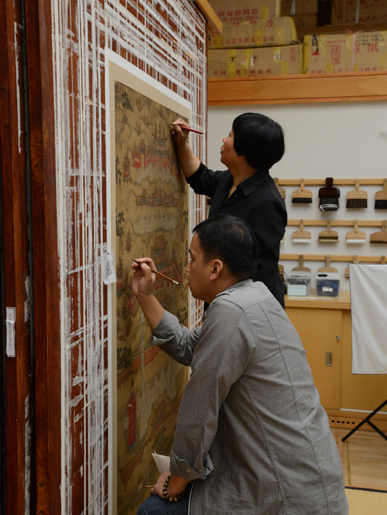 Mrs Qiu and Mr Chu Hao retouching the painting on the drying board.