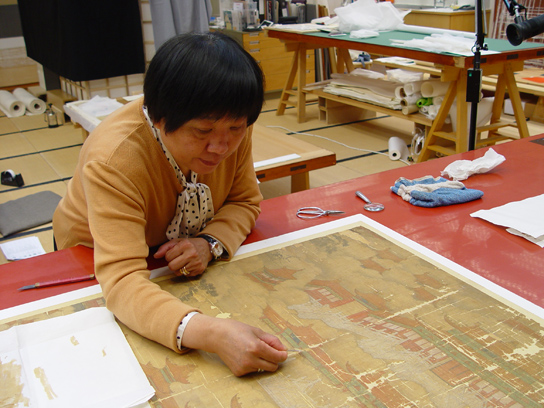 Mrs Qiu repairing the missing silk areas