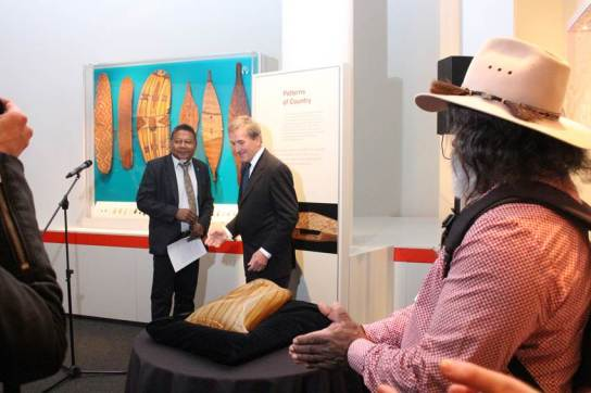 Abe Muriata watches as British Museum Director Neil MacGregor accepts a gift from Peter Yu, Chair of the National Museum of Australia Indigenous Reference Group.