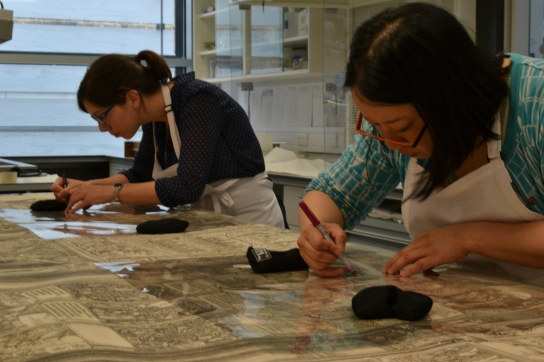 Conservators, Emma Webb (left) and Megumi Mizumura (right) mapping out damage to individual pages of Dürer's Triumphal Arch.