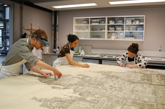 Conservation student placements, Tom Bower (left), Carina Rosas (centre) and Lauren Buttle (right) surface-cleaning Dürer's Triumphal Arch.