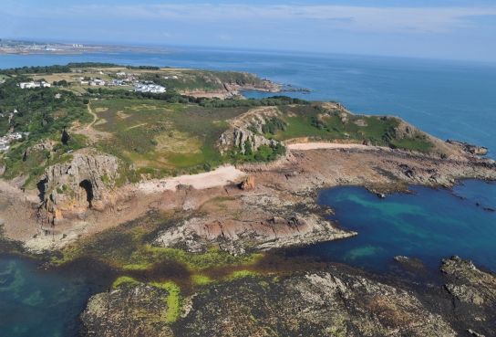 An aerial view of Jersey, facing east, taken by Ice Age Island project imaging specialist Sarah Duffy on a low (spring) tide which exposed much of the rocky, offshore landscape. The early Neanderthal site of La Cotte de St Brelade is the cave cut into the cliffs on the left of the picture. (Photo: Sarah Duffy)